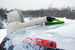 Woman clears snow from the roof of the car Royalty Free Stock Images