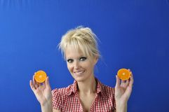 Woman with a clementine Stock Images