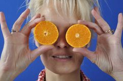 Woman with a clementine Royalty Free Stock Images