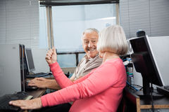 Woman Clenching Fist While Looking At Man In Computer Class Stock Images