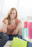 Woman Clenching Fists With Shopping Bags On Sofa Stock Photography