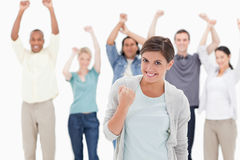 Woman clenching her fist with people behind raising their arms Stock Photography