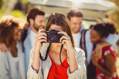 Woman clicking a photo from camera in park Stock Photography