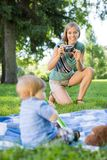 Woman Clicking Picture Of Baby Boy In Park. Happy mid adult women clicking picture of baby boy in park stock photos