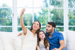 Woman clicking selfie with family on sofa Royalty Free Stock Images