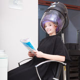 Woman client curlers  in hair reads magazine hairdressing beauty salon. Stock Photo