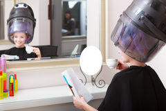 Woman client curlers  in hair reads magazine hairdressing beauty salon. Stock Image