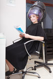 Woman client curlers  in hair reads magazine hairdressing beauty salon. Stock Images