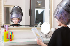 Woman client curlers  in hair reads magazine hairdressing beauty salon. Royalty Free Stock Image