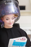 Woman client curlers  in hair reads magazine hairdressing beauty salon. Stock Photography