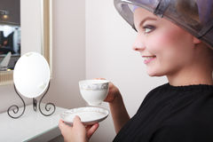 Woman client drinking coffee tea in hairdressing salon. Girl in hair rollers curlers with hairdryer. Young woman female client drinking hot drink coffee tea in Royalty Free Stock Images