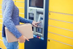 Woman using automated self service post terminal machine or lock stock images