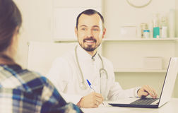 Woman client visiting consultation with man doctor Stock Photos