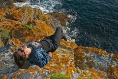 Woman on a cliff. At the seaside looking at the photographer Stock Photo