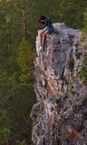 Woman on cliff. Young woman sitting on the edge at the top of a high, sheer cliff Royalty Free Stock Image