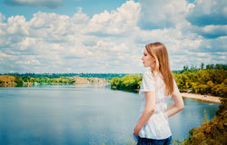 Woman at cliff above the river Royalty Free Stock Photo