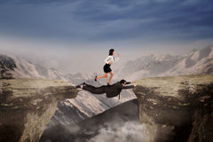 Woman through the cliff helped by her friend Royalty Free Stock Images