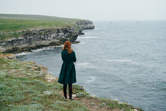 Woman on the cliff of the mountain by the sea, sadness, wind Stock Image