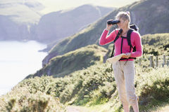 Woman on cliffside path using binoculars Stock Photos