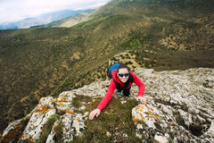 Woman climber is climbing on a rock Stock Photography