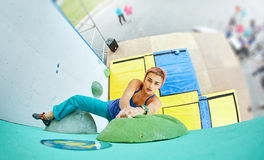 Woman climber climbs a bouldering problem on climbing gym Royalty Free Stock Image