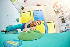 Woman climber climbs a bouldering problem on climbing gym Royalty Free Stock Images
