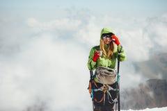 Woman climber drinking tea on mountain Stock Image