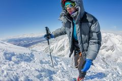 Woman climber in helmet and down jacket with trekking sticks goes uphill at dawn.  Royalty Free Stock Image