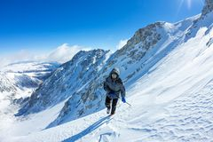 Woman climber in helmet and down jacket with trekking sticks goes uphill at dawn.  Stock Photo