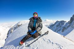 Woman climber in helmet and down jacket with trekking sticks sits on top of a mountain Royalty Free Stock Photo