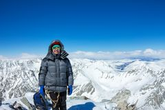 Woman climber in helmet and down jacket with trekking sticks stand on top of a mountain Stock Photo