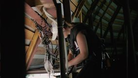 Woman climber inside the roof. Professional steeplejack wearing the outfit is inside the roof of the building. Young climber prepares equipment for work stock footage