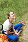 Woman climber seats on the grass and looking up Royalty Free Stock Image