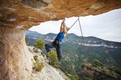 Woman climber struggling to make next movement up Stock Photo