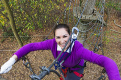 Woman climbing in adventure park. Young woman climbing in adventure park Royalty Free Stock Photography