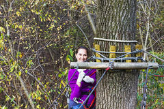 Woman climbing in adventure park. Young woman climbing in adventure park Royalty Free Stock Images