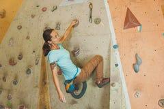 Woman climbing artificial boulder indoors Stock Images