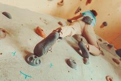 Woman climbing artificial boulder Stock Photo