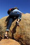 Woman Climbing Boulder in High Heel. A woman in high heel shoes and a backpack is climbing up a big boulder in outback Australia Stock Image