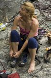 Woman with climbing equipment. Middle aged blond woman putting on rock climbing shoes with equipment in background on rocky mountainside Stock Image