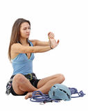Woman in climbing equipment. Attractive woman in climbing equipmant limber up in white background Royalty Free Stock Photo