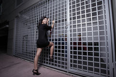 Woman climbing the fence Stock Photography
