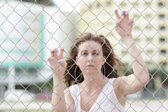 Woman climbing the fence Royalty Free Stock Photos