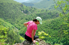 Woman climbing in the  green mountain Stock Image