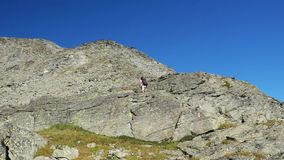 Woman climbing on high altitude rocky mountain cliff. Summer adventures on the Italian French Alps. stock video footage