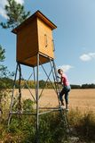 Woman climbing on high seat for hunters stock photo