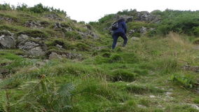 Woman climbing hill slope stock footage