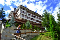 Woman climbing hilltop building stairs. Mature tourist woman climbing stairway to new hotel perched on hilltop at Bulgarian Rhodopes mountains Shiroka laka Stock Image