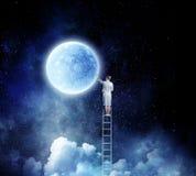 Woman climbing ladder Stock Photo