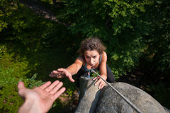 Woman climbing on large boulder, her partner giving her hand. Young fearless woman climbing on large boulder, her male partner giving her a hand. Helping hand Stock Photos